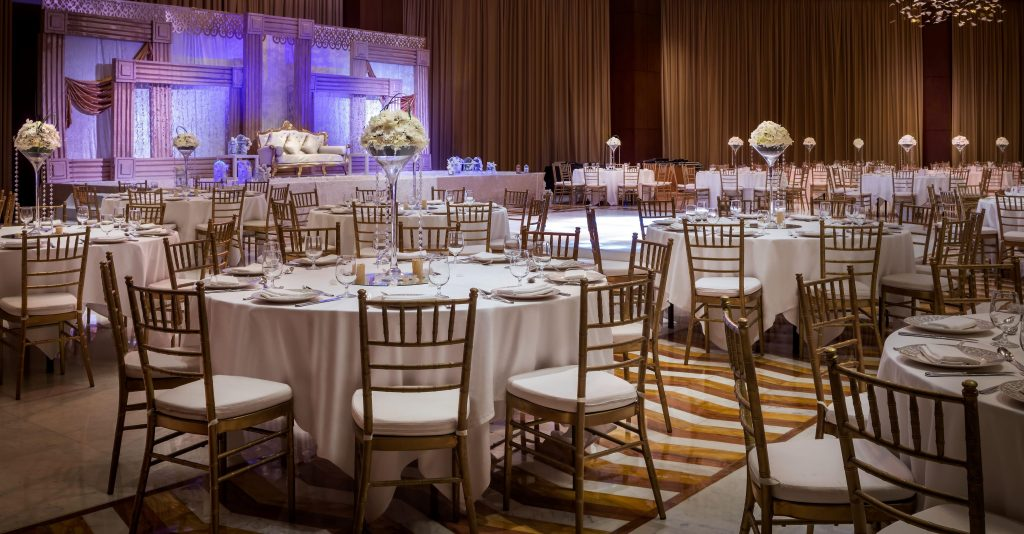Large wedding ballroom reception hall with rounds of 9 tables with tall floral bouquets and a raised stage with elegant couch for the guests of honor