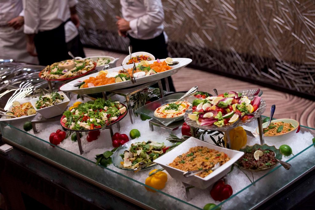 Elegant buffet of salads and appetizers in ceramic serving dishes and bowls in a bed of ice with vegetables
