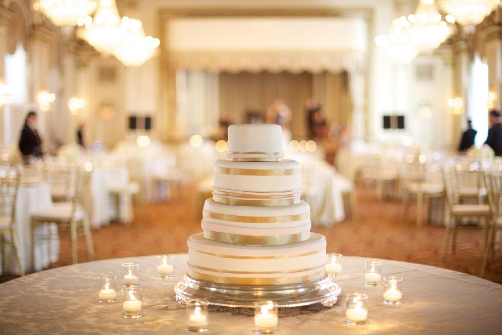 Close up of multi-tiered wedding cake with gold stripes surround by tea light candles on lace covered table