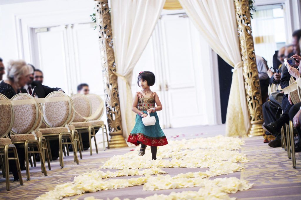 Adorable flower girl in Indian dress walking down petal covered aisle in front of floral draped pillars with rows of guest on each side