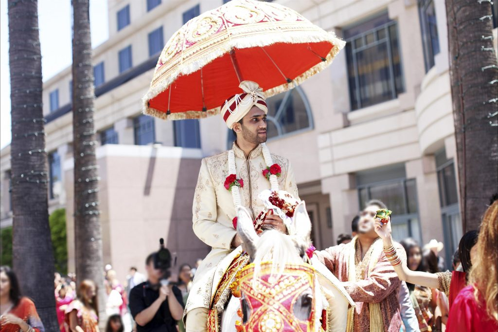 Groom adorned in Indian wedding styled garb riding atop a decorated horse outside surrounded by costumed wedding guests