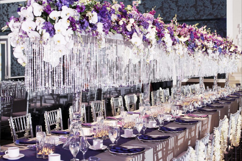 Massive floral topped chandelier with hanging crystal beads over a long banquet table with extravagant place settings and floral accented chairs