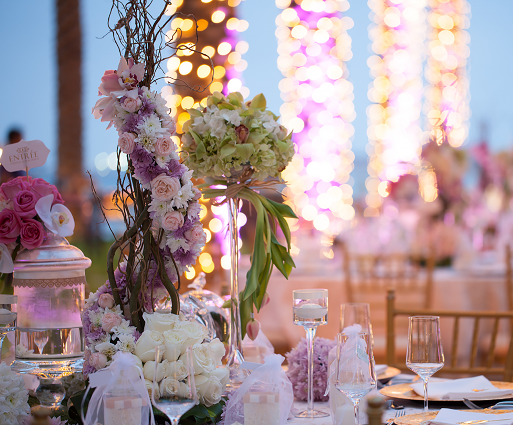 Close up of guest table with tall floral bouquet arrangements, glassware, and elegant place settings