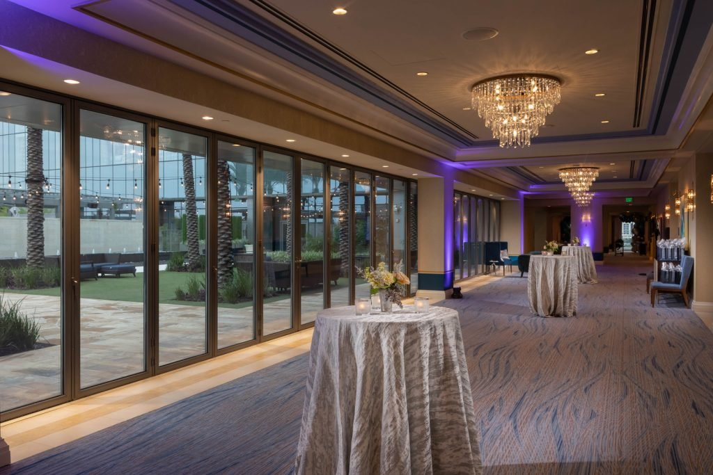 Prefunction foyer with standing tables spread widely out down long hall with several chandeliers with large windows showing patio