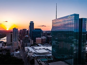 Aerial view of sunset and downtown reflected in glass façade of Fairmont Austin
