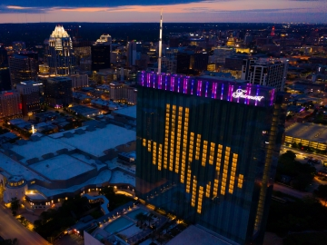 Night aerial view of downtown and Fairmont Austin with rooms lights lit to make the shape of Texas and Austin as its heart