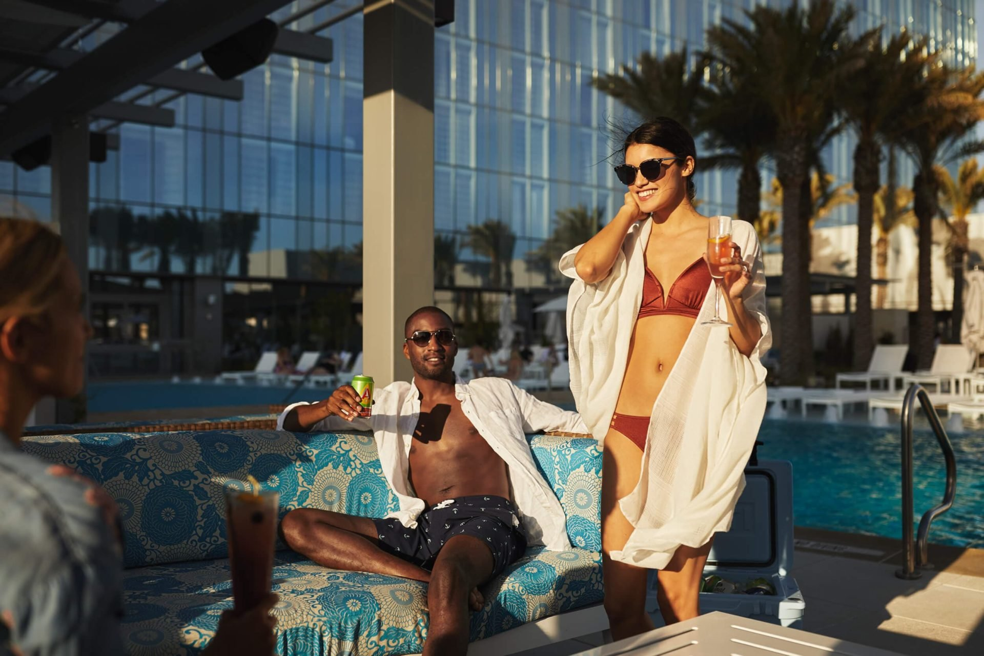 Smiling couple brightly lit by facing sunset while enjoying drinks and conversation in VIP Cabanas with pool and exterior in the background
