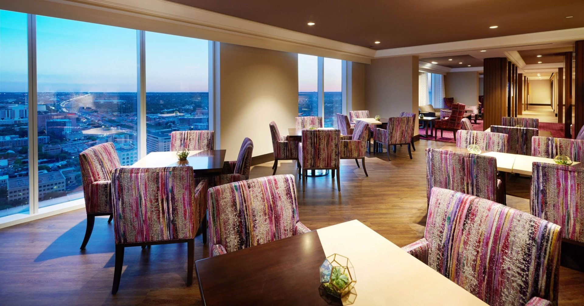 Lounge with Groups of 4 tables under recessed ceiling lights and window featuring amazing evening city view
