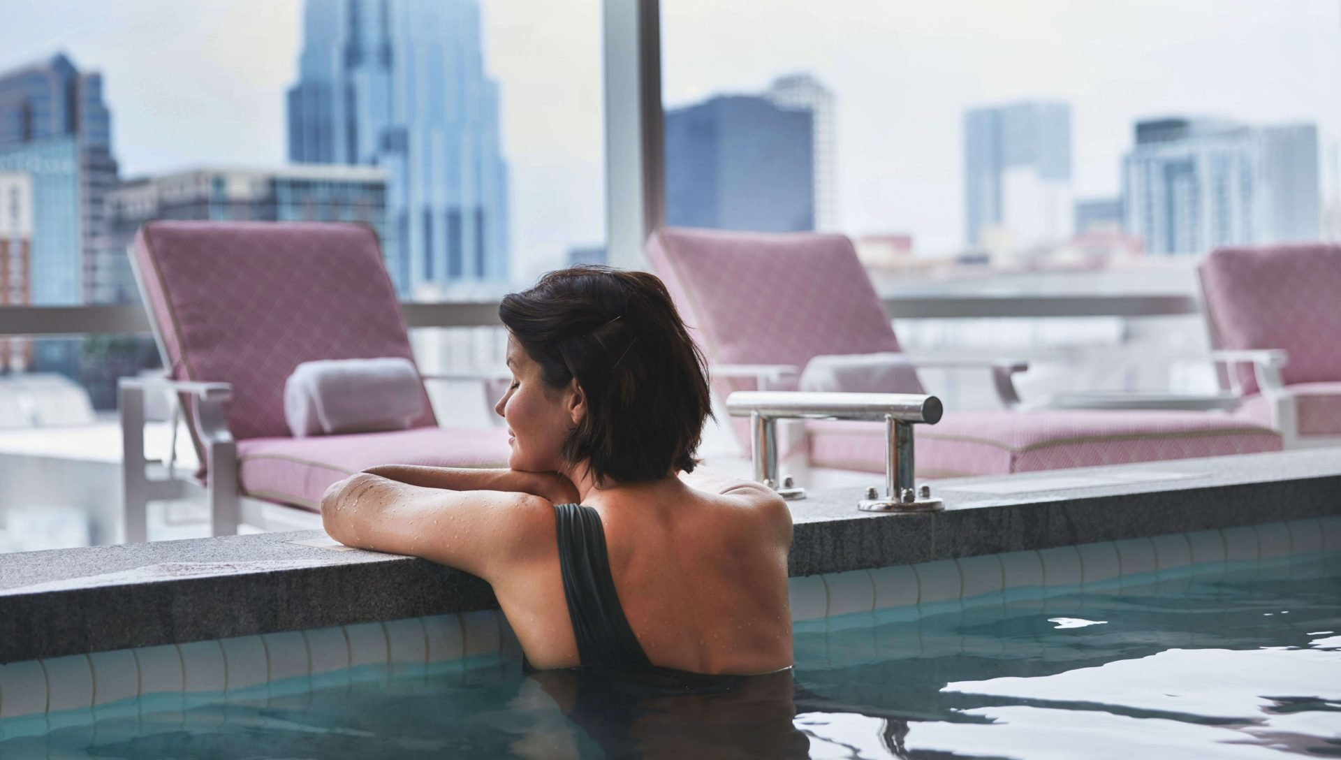 Woman relaxing along soaking spa edge looking out to lounge chairs and oversized city scape view