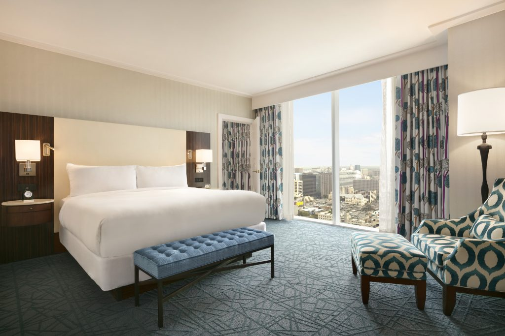 Angled view of king size bed with nightstands, large downtown view, and relaxing armchair with footstool and lamp