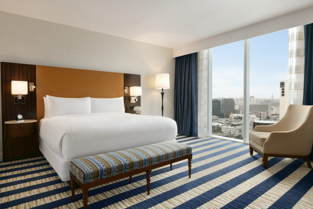 Full view of king size bed with nightstands, lamp, large downtown view, and relaxing armchair