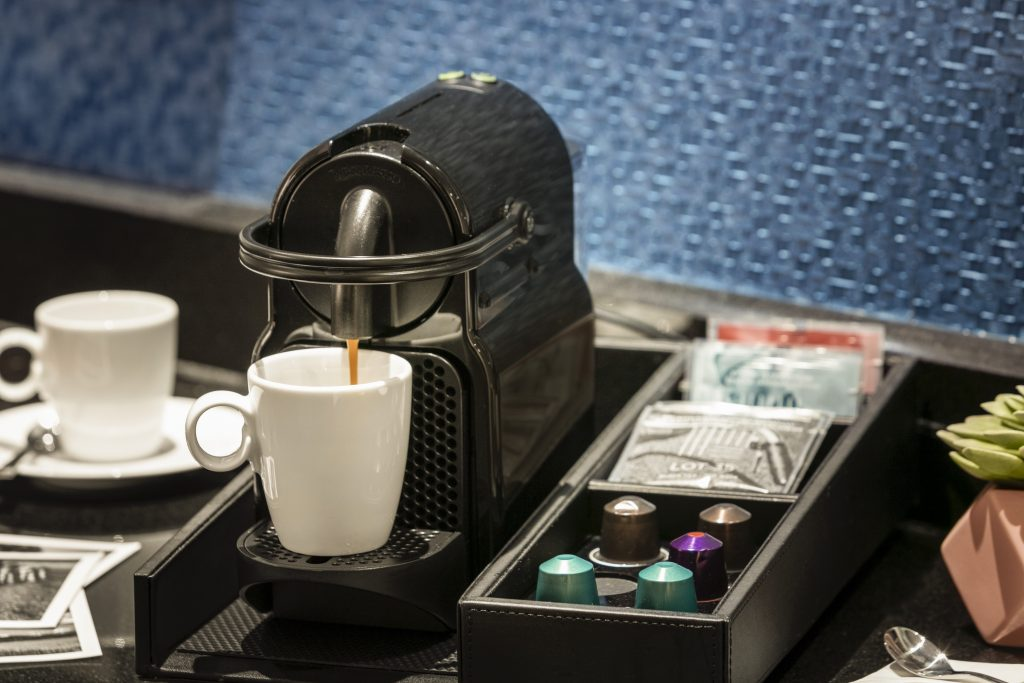 Coffee being brewed into a cup by in-room deluxe instant brewing machine accompanied by tray of variety of premium coffee selections