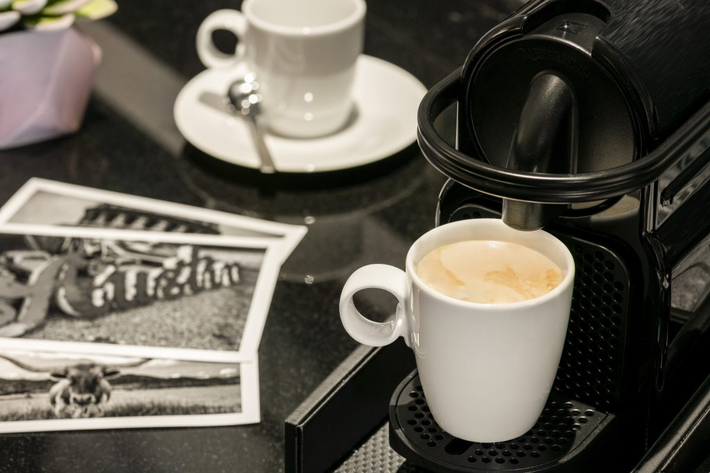 Close up of fresh brewed coffee from in-room deluxe instant brewing machine on table with cup and saucer in background