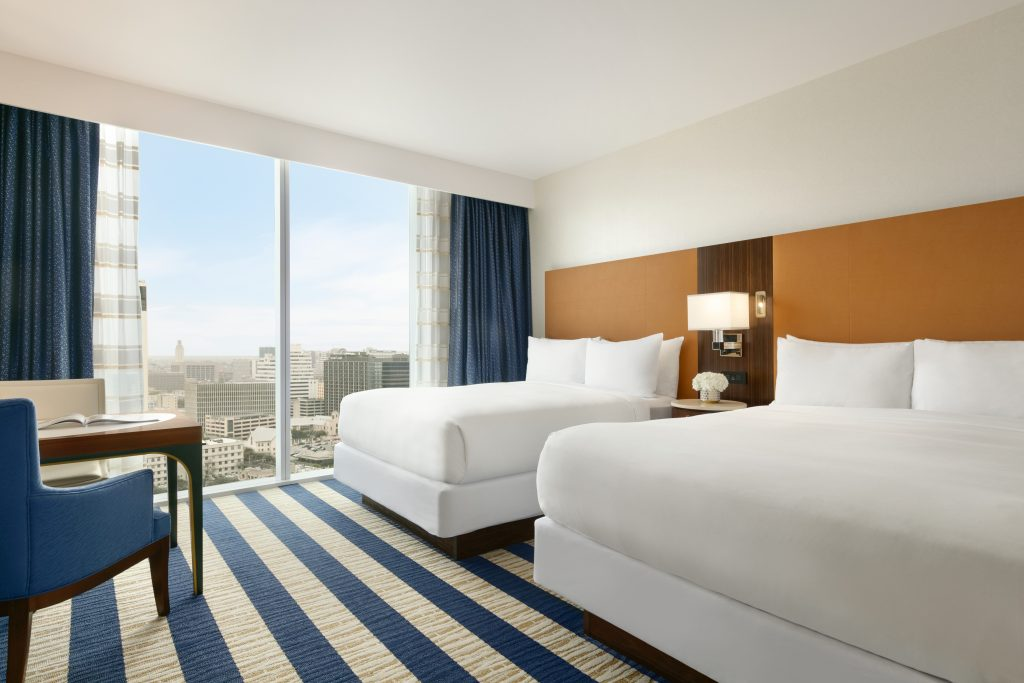 Angled view of table with 2 chairs, large downtown cityscape view and 2 queen beds
