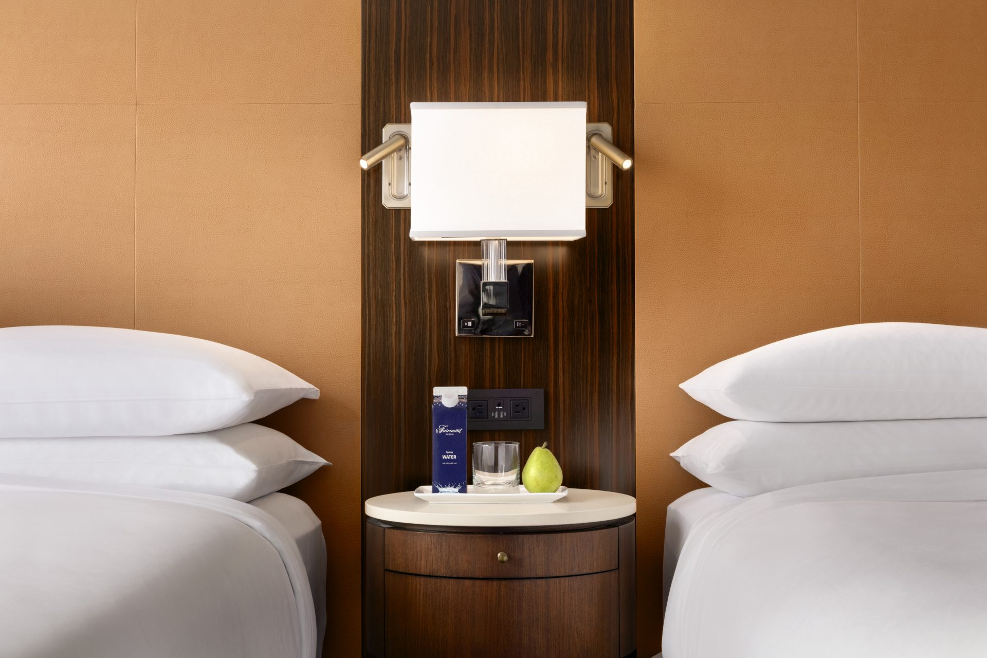 Nightstand with 2 personal reading lights, convenient power outlets, and complimentary water and fruit between 2 queen beds
