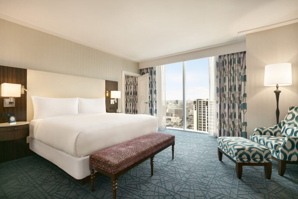 Full view of king size bed with nightstands, large downtown view, and relaxing armchair with foot stool and lamp