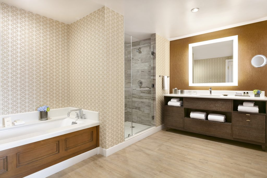 Bathroom showing large marble whirlpool bathtub next to shower with glass door next to sink area with cabinets and large mirror