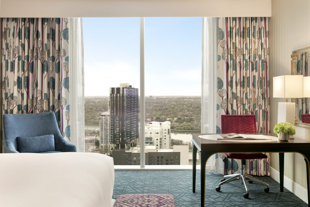 Side view of Gold King Studio Suite with large downtown view, worktable with rolling chair, bouquet, and lamp