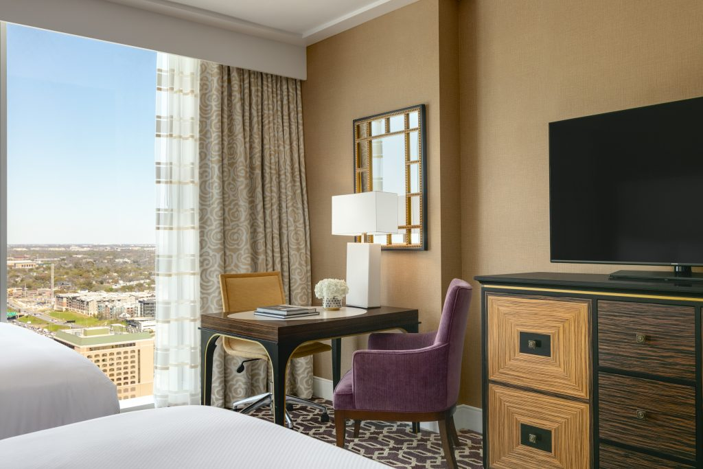 View from bed of large downtown view, table with 2 chairs bouquet and lamp next to dresser with flatscreen