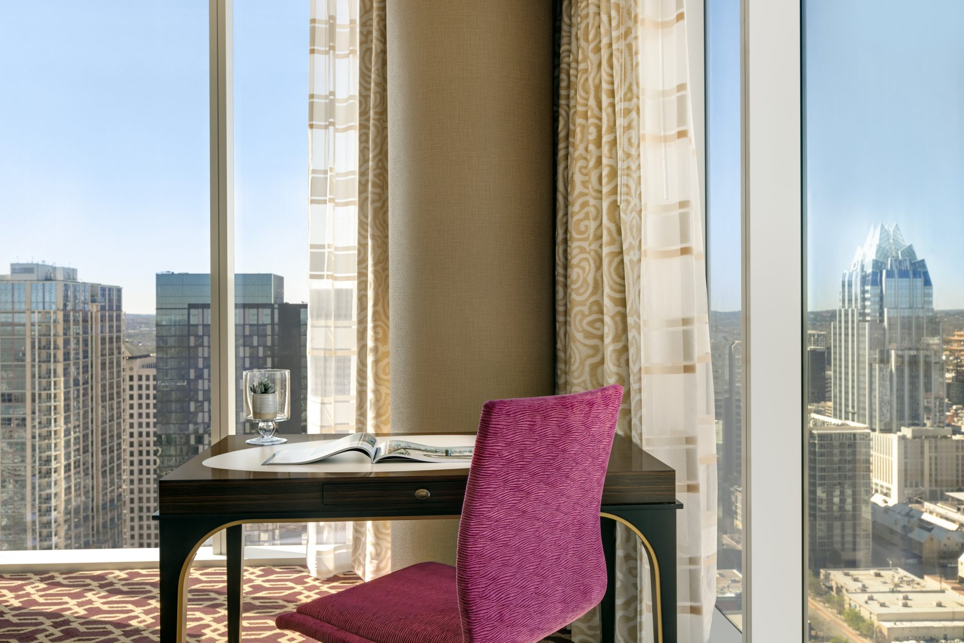 Elegant personal worktable and chair set in the corner of a floor to ceiling wraparound view of downtown area