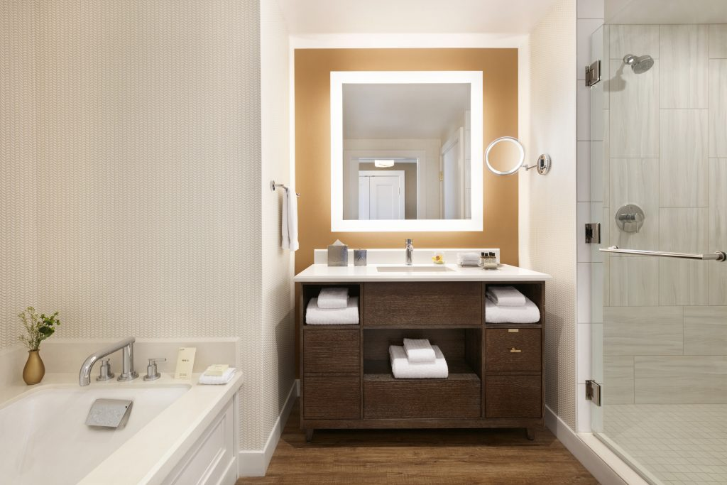 Bathroom showing large marble whirlpool bathtub, inset sink area with cabinets and large mirror next to large shower with glass door