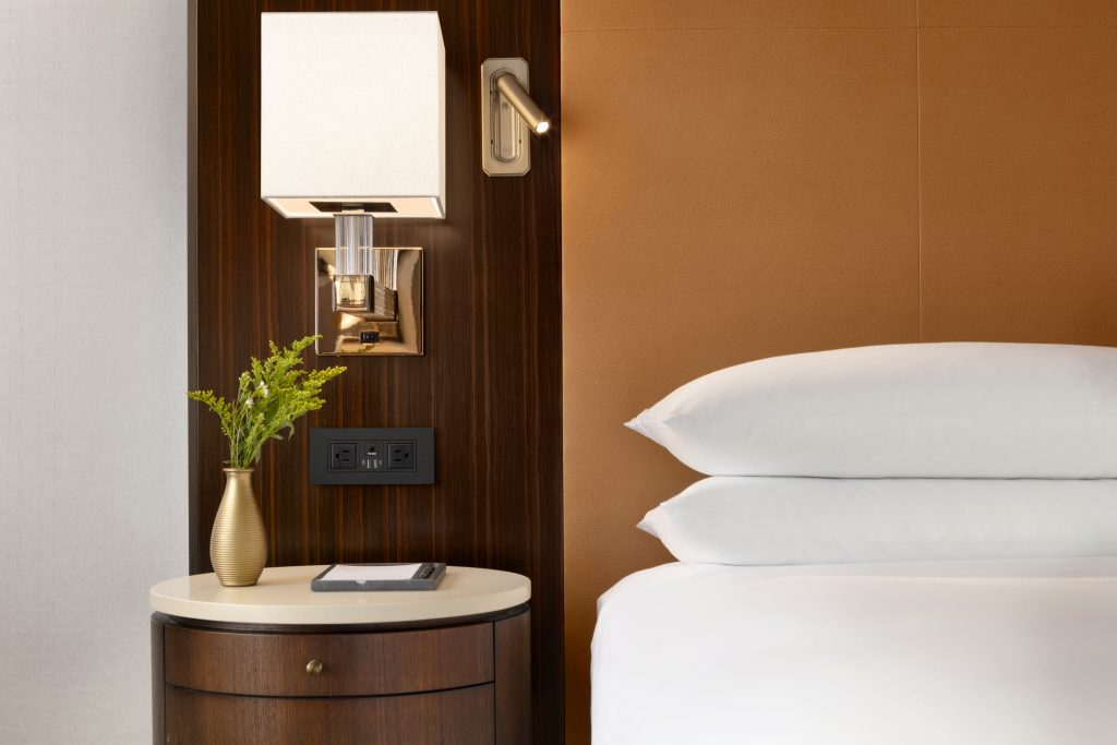 Nightstand with accent lighting, personal reading light, convenient power outlets, and vase next to bed with pillows
