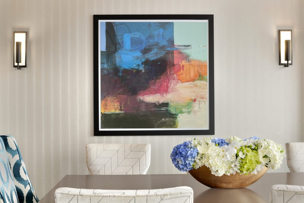 View of dining table with chairs and bouquet in front wall with modern artwork and wall sconces