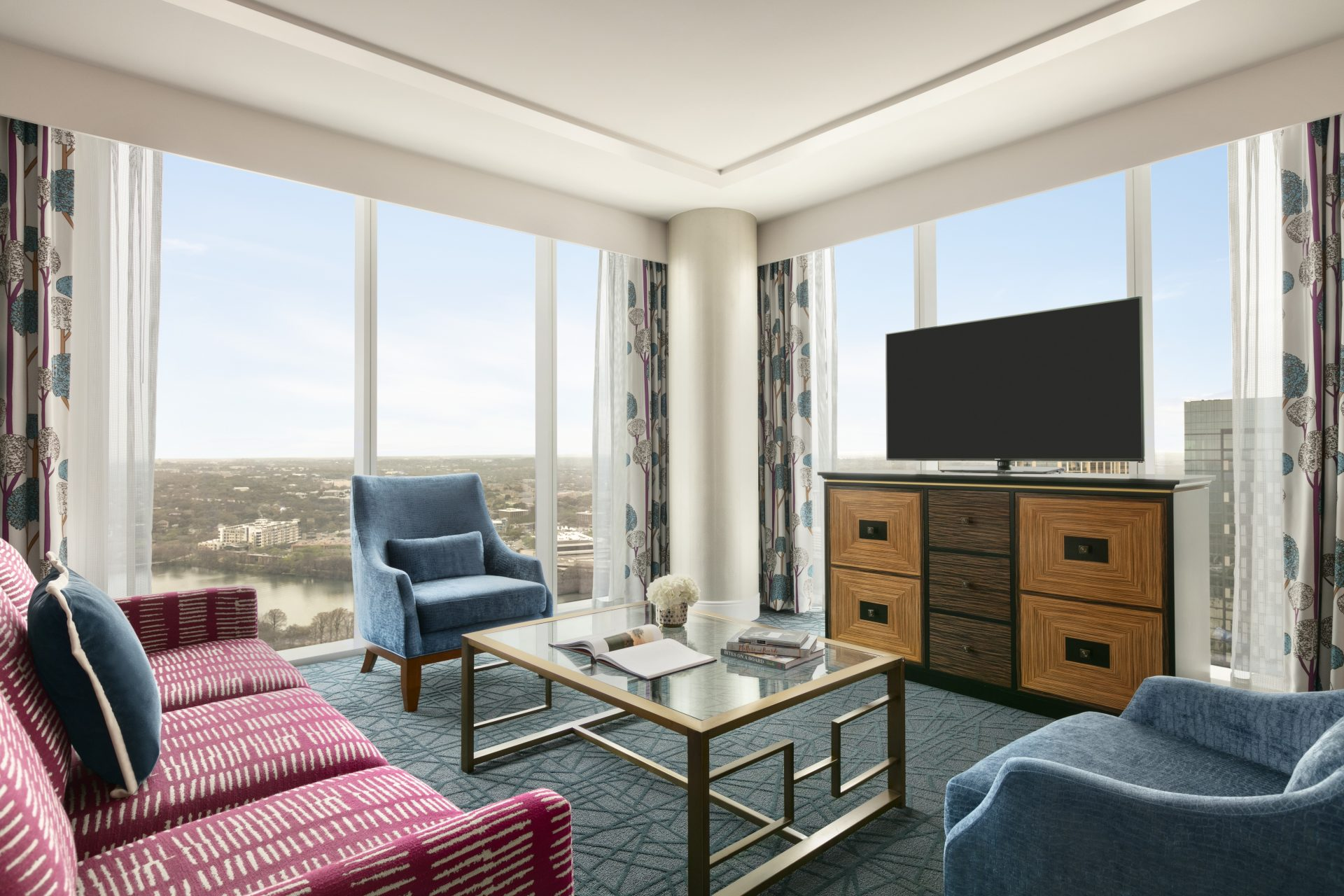 Angled view of Grand suite lounge area with couch, 2 armchairs, coffee table, flatscreen on a dresser and a wrap around downtown view