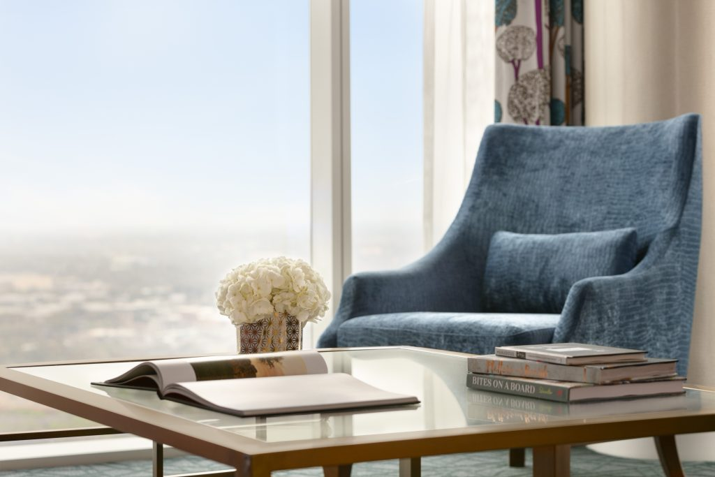 Relaxing armchair in front large window/city view with glass coffee table, bouquet and books