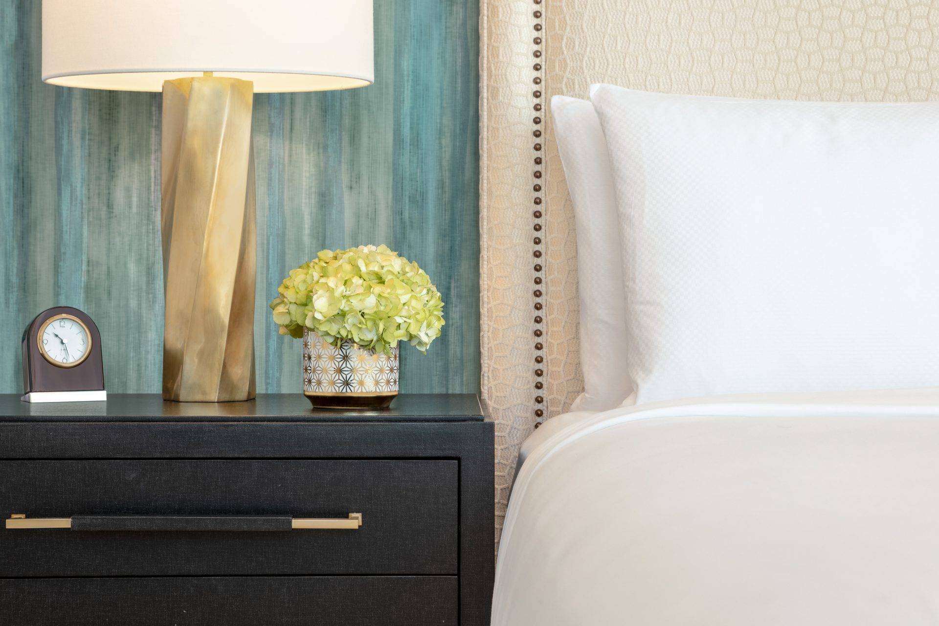Close up view of end table with clock, twisted brass lamp, bouquet next to luxurious bed