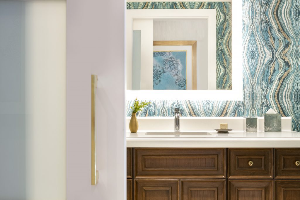 Bathroom counter view showing large backlit mirror, sink with polished metal fixtures, marble top and wood cabinets