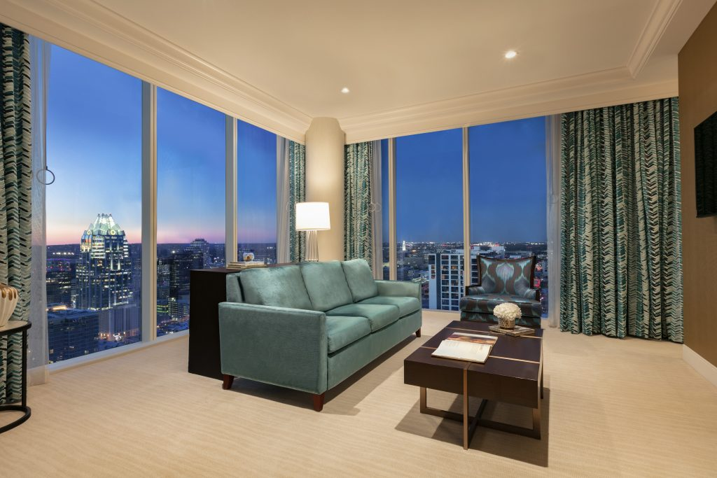Lounge area of Presidential Suite with couch, armchair, and table with wraparound downtown evening city view