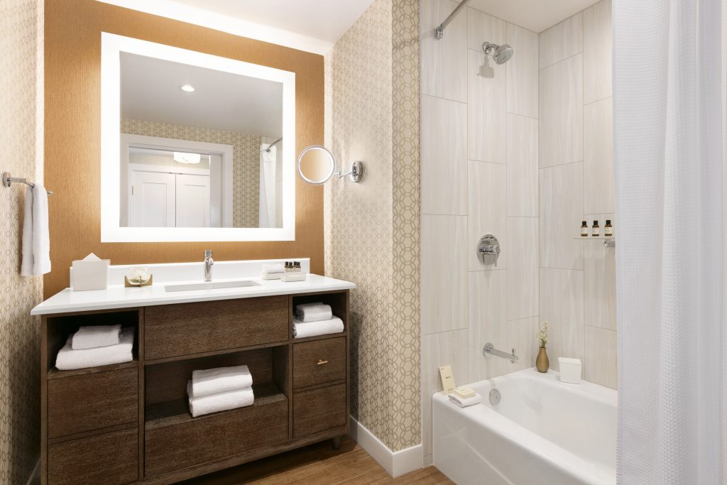 Bathroom with glass inset sink and cabinets with backlit large mirror, personal mirror and next to shower/bathtub