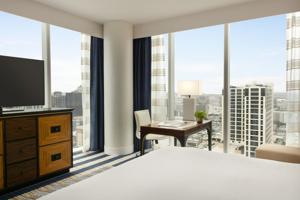 Angle view from bed of dresser with flatscreen, worktable with leather rolling chair, and wraparound city view from the large windows
