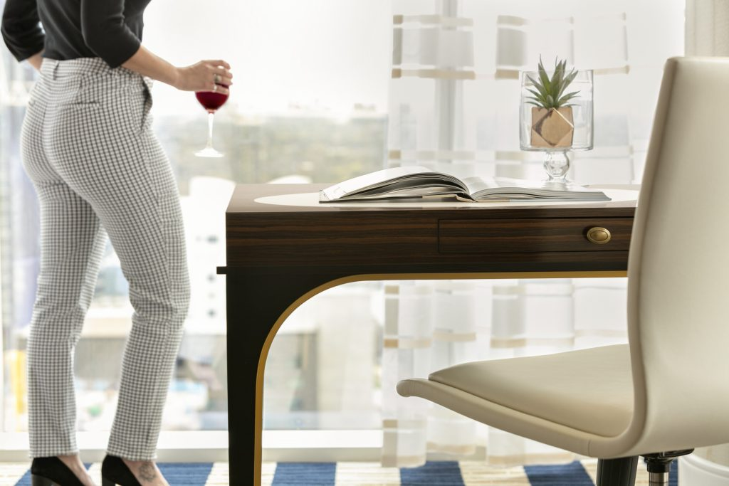 Close up view of a woman holding a wine glass taking in the city view from the large window next to a worktable with leather rolling chair