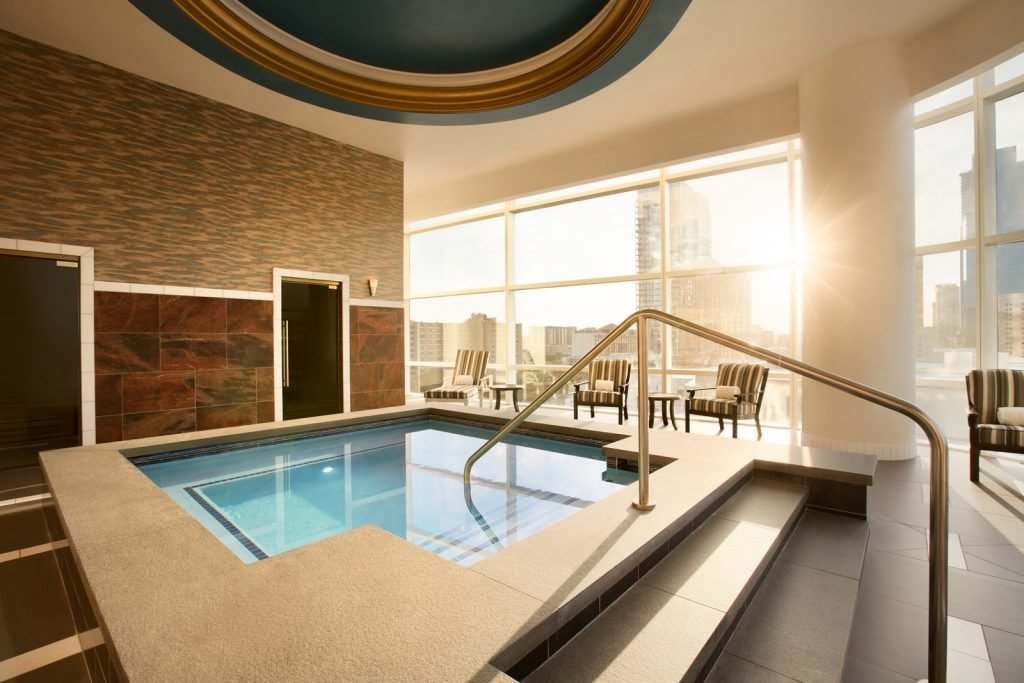 Large soaking pool next to men's & women's private areas entrances in front of large city scape view windows