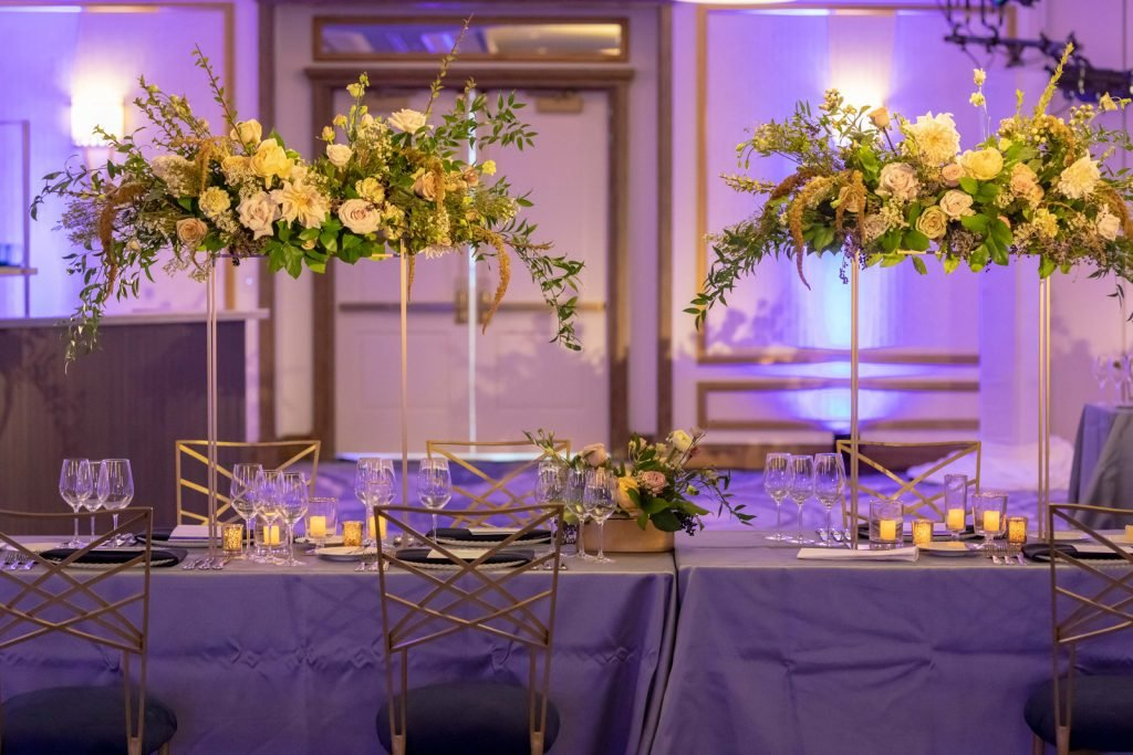 Side view of long banquet table and chairs with silk table cloth, place settings, and raised height floral centerpieces