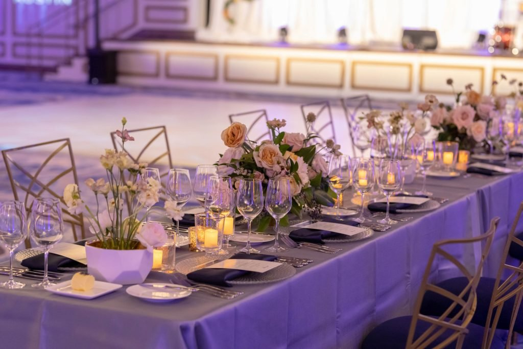 Long banquet table and chairs with silk table cloth, place settings, multiple floral centerpieces and with stage in background