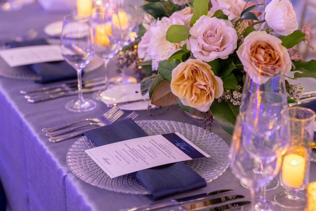 Close up of elegant banquet place setting, dining menu placed on plate, floral bouquet, and tealights