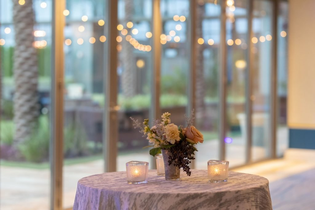 Focus on standing table in prefunction area with floral bouquet and tealights with large window with patio view