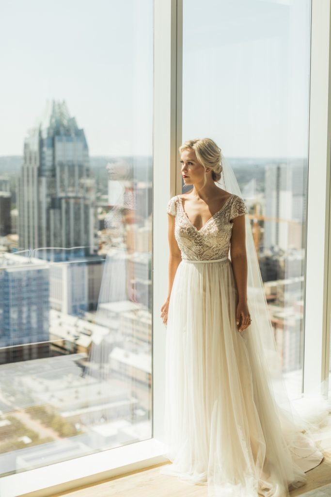 Bride with long flowing veil standing next to and looking out of oversized window with scenic view of downtown buildings