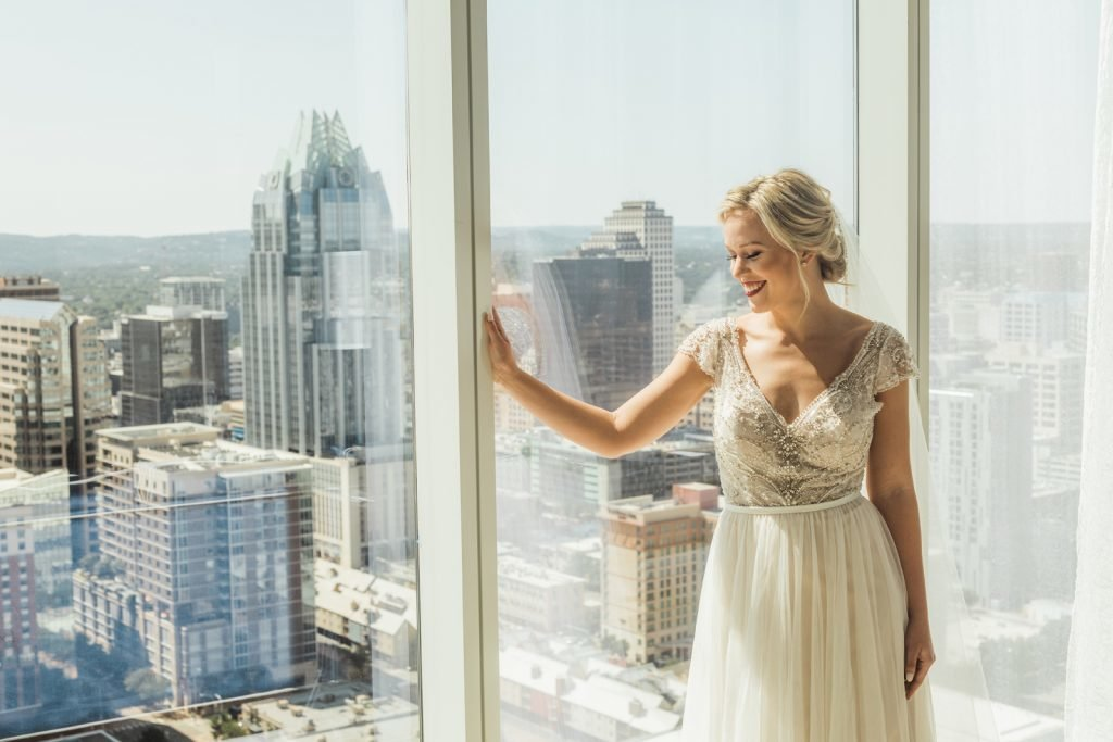 Smiling bride holding hand gently against window frame of oversized window with scenic view of downtown buildings