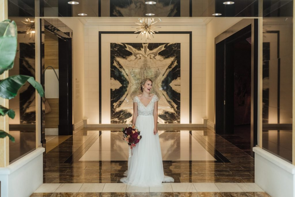 Laughing and smiling bride in wide view of marble lobby holding bouquet