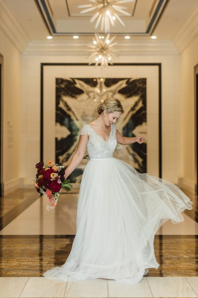 Bride in marble lobby with flowing wedding dress holding bouquet smiles while looking down
