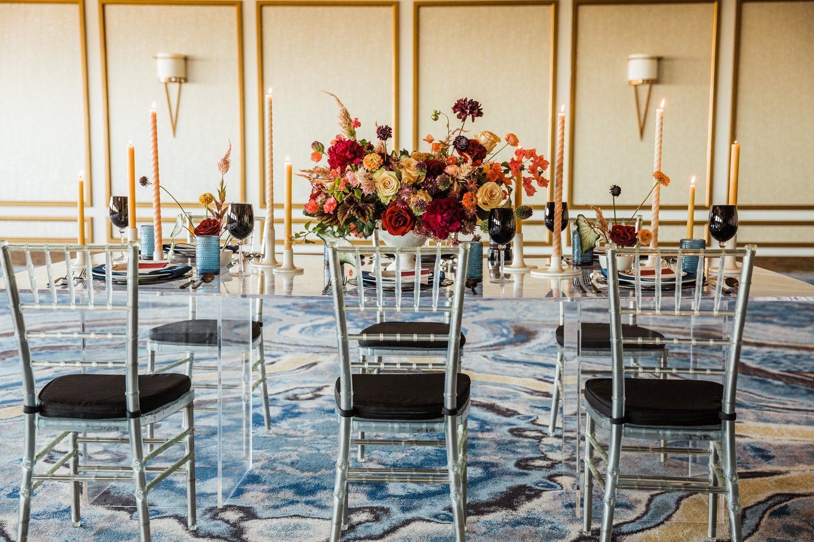 Glass table in ballroom with 6 chairs and fine place settings, floral centerpiece and several lit candles