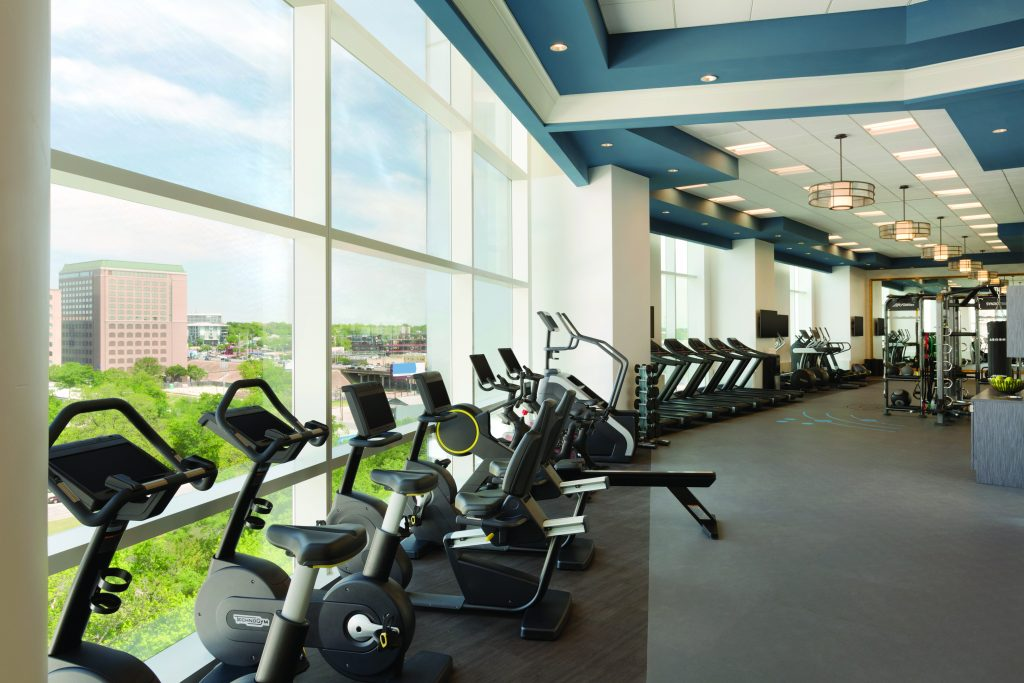 Long Row of exercise bikes, treadmills, stair climbers and other fitness equipment looking out large windows with scenic city scape view