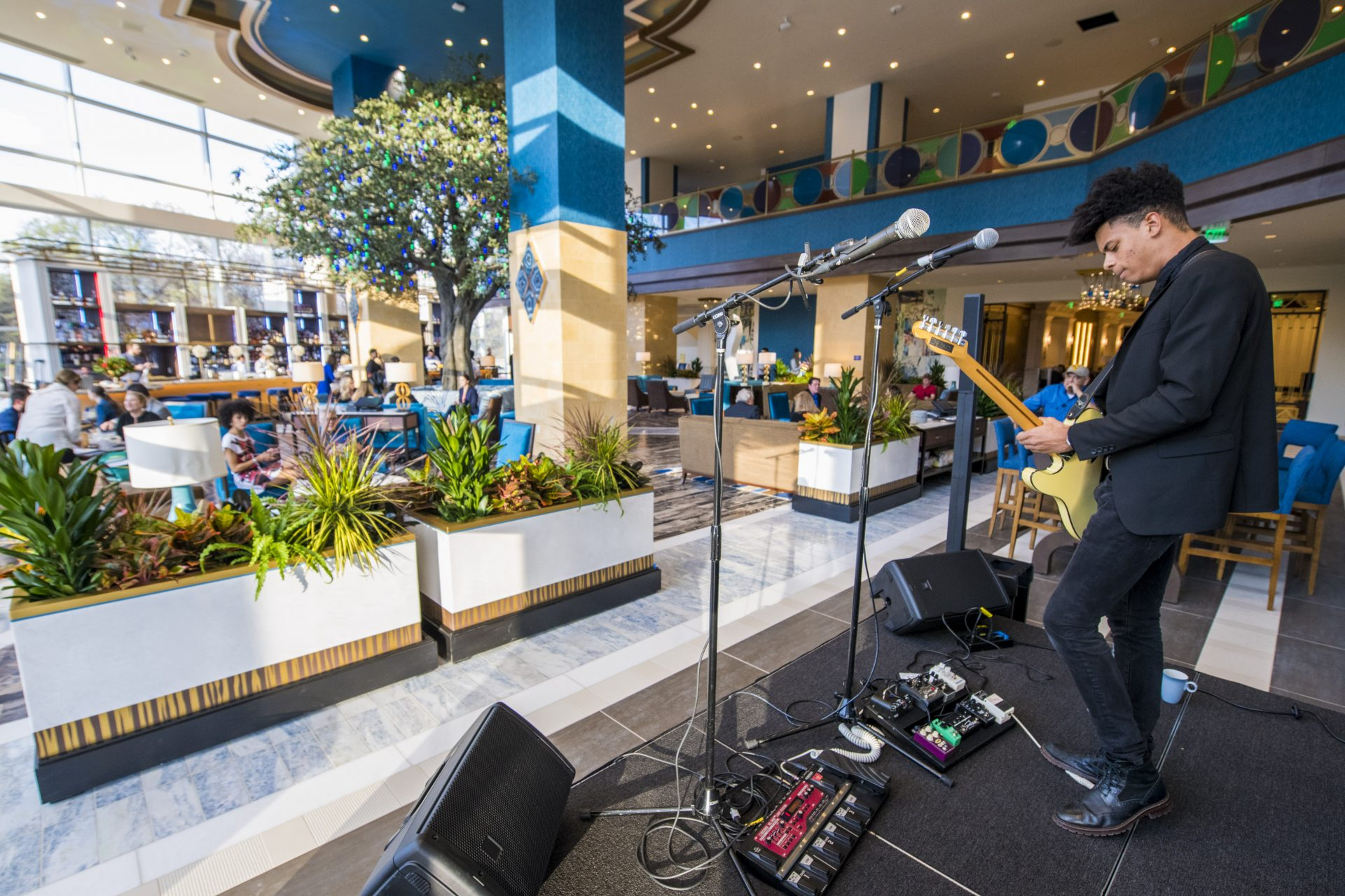View from stage of musician playing electric guitar looking out to large open Fulton restaurant seating area and balcony