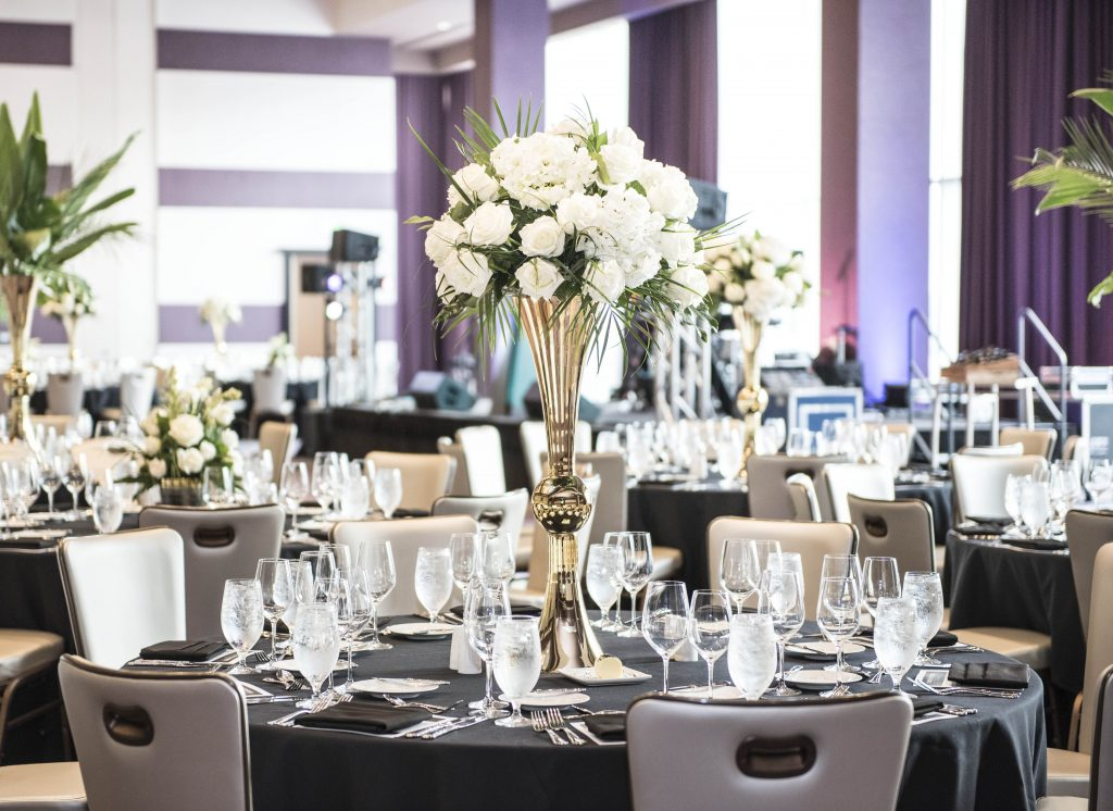 Round banquet tables with elegant place settings with tall floral bouquets with raised stage in background