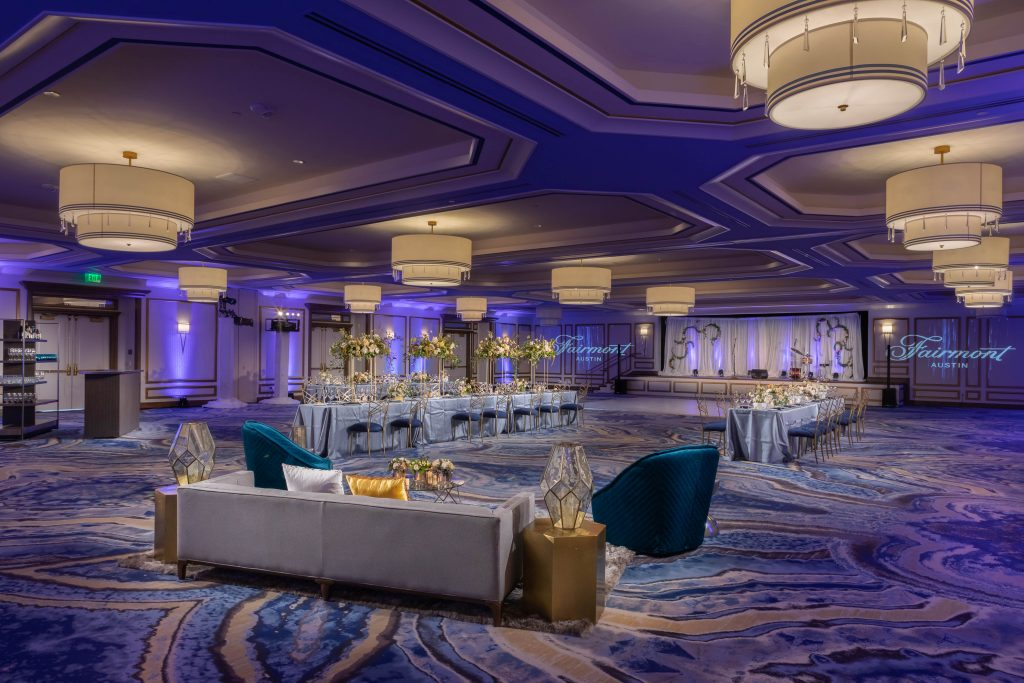 Wide view of Palm Park ballroom with large open space, stage, round chandeliers, 2 long banquet tables with chairs and guest of honor couch seating area
