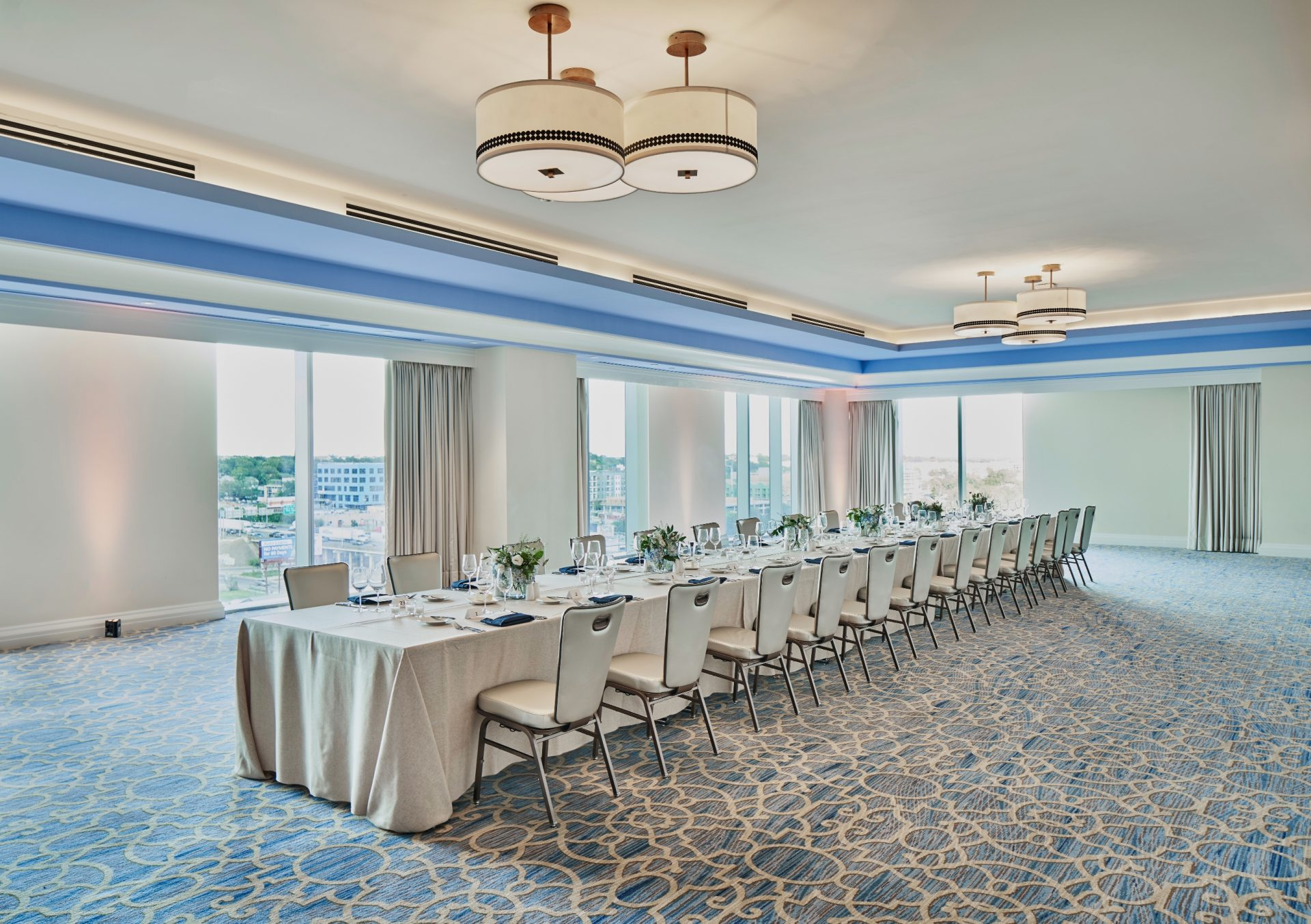 Wide view of long banquet table next to oversized windows with sweeping views of downtown Austin